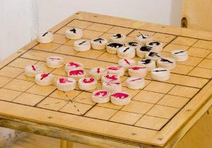 Доска лакирована, на шашки нанесены пиктограммы