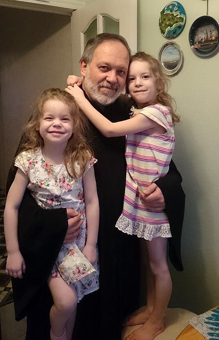 Священник Александр Дьяченко с внучками. Фото из личного архива.