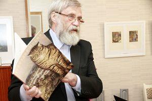 Алексей Мосин на выставке работ отца с альбомом в руках